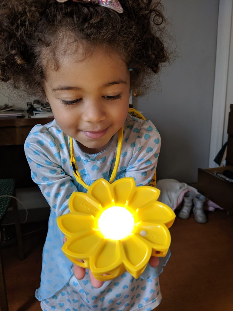 Young girl holding flower toy that lights up