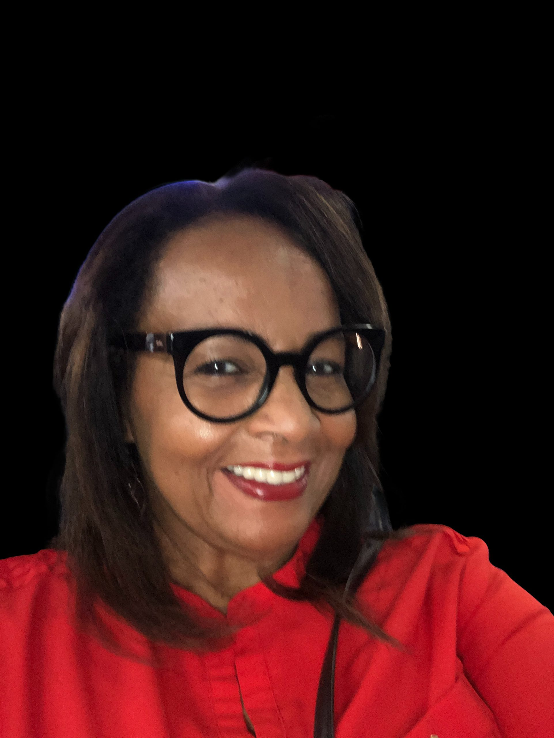 Shelia Dudley smiling with black round glasses and a red shirt